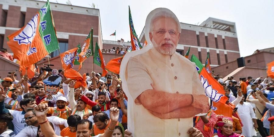 BJP supporters carry a cut-out of PM Narendra Modi.