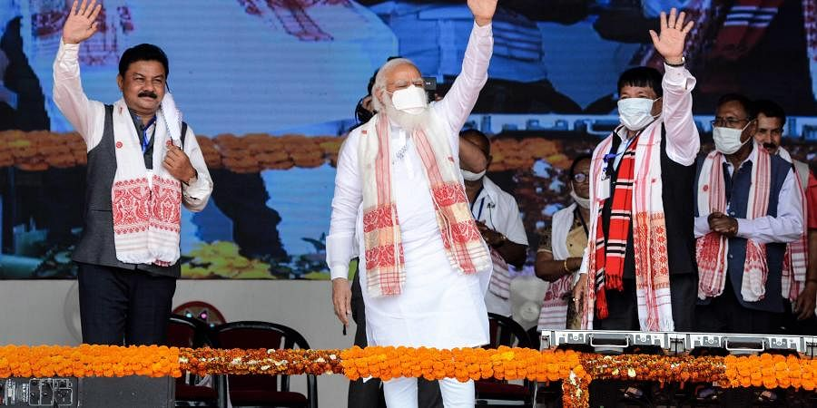 Prime Minister Narendra Modi waves at crowd during his election campaign rally for Assam Assembly polls, at Kamargaon in Golaghat, Sunday