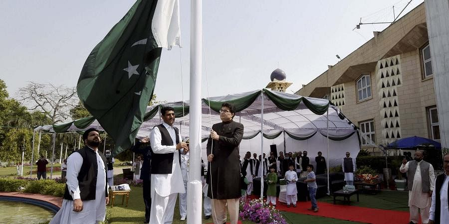 Charge d' Affaires for Pakistan High Commission Aftab Hasan Khan hoists his country's flag on the occasion of Pakistan Resolution Day, at Pakistan High Commission, in New Delhi, Tuesday