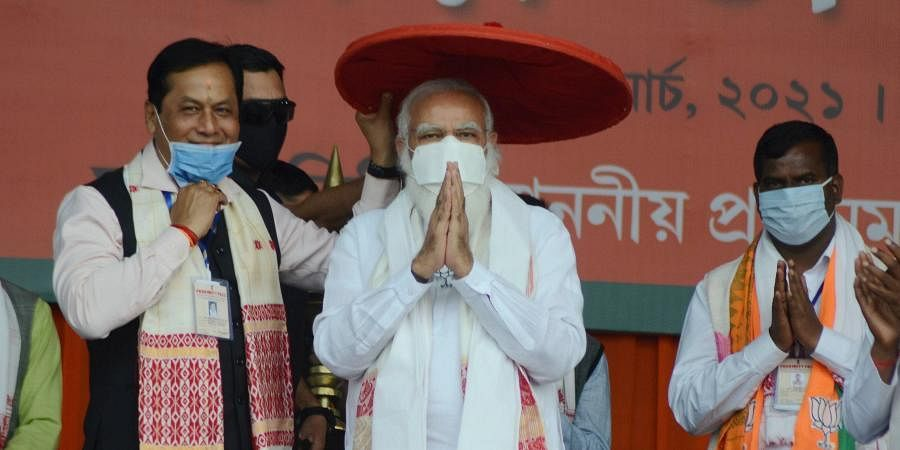 PM Narendra Modi being presented an 'Assamese Japi' by Assam CM Sarbananda Sonowal during a public rally ahead of Assam Polls