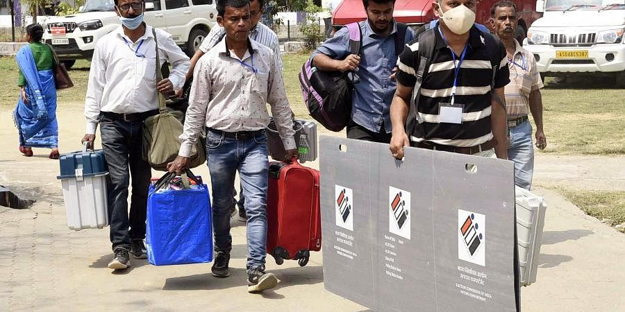 Polling officials carry Polling material as they leave from a distribution center, ahead of the first phase of Assam assembly polls in Jorhat on Friday.