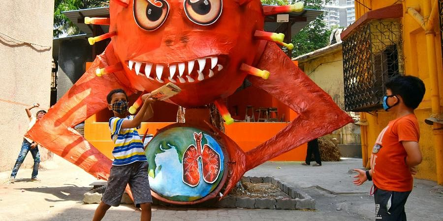 Children play near a giant demon to create awareness of COVID-19 on the eve of the Holi festival, in Mumbai on Sunday.