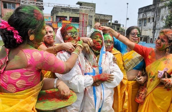 Women, wearing PPE kit, play with dry colours during the Holi festival, as coronavirus cases spike across the country, at Begumbazar in Kolkata. (Photo   PTI)