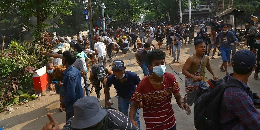 Anti-coup protesters disperse as the protesters confront police in Yangon, Myanmar.