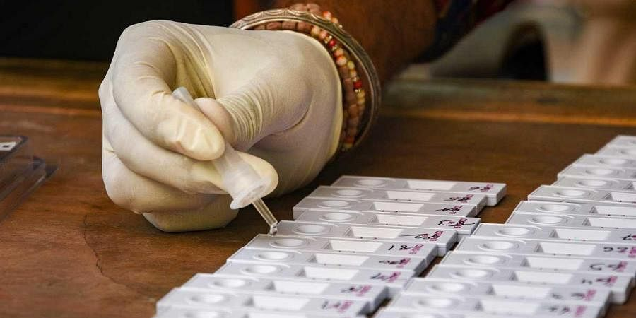 A health worker conducts COVID-19 Rapid Antigen test at the district administration office, coronavirus