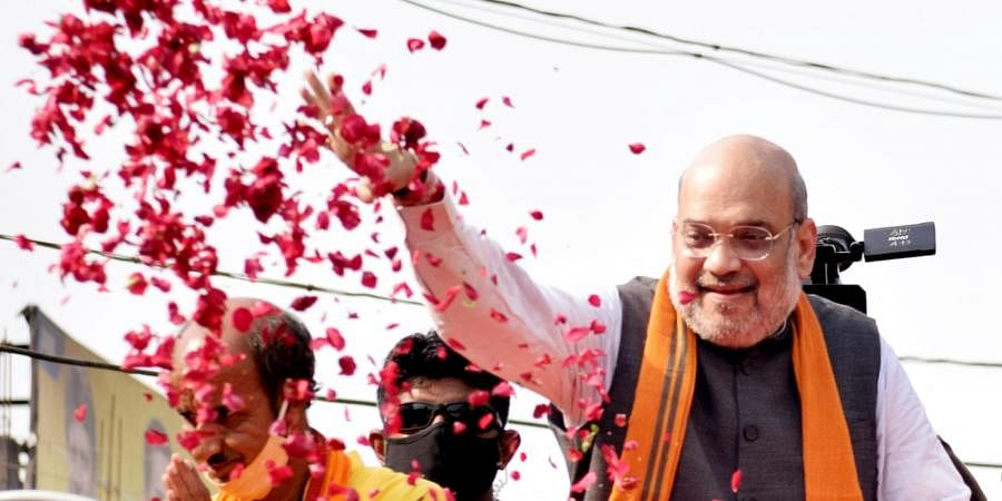 Union Home Minister Amit Shah throws flower petals during a roadshow ahead of the second phase of Assembly elections at Debra, in West Medinipur.