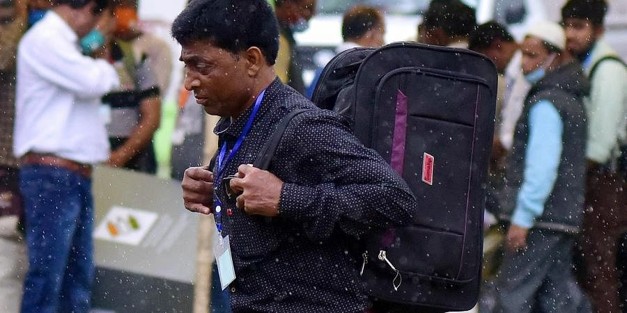 Polling Officials walk in the rain as they collect EVMs and other polling materials ahead of the second phase of the Assam Assembly elections, in Nagaon on Wednesday
