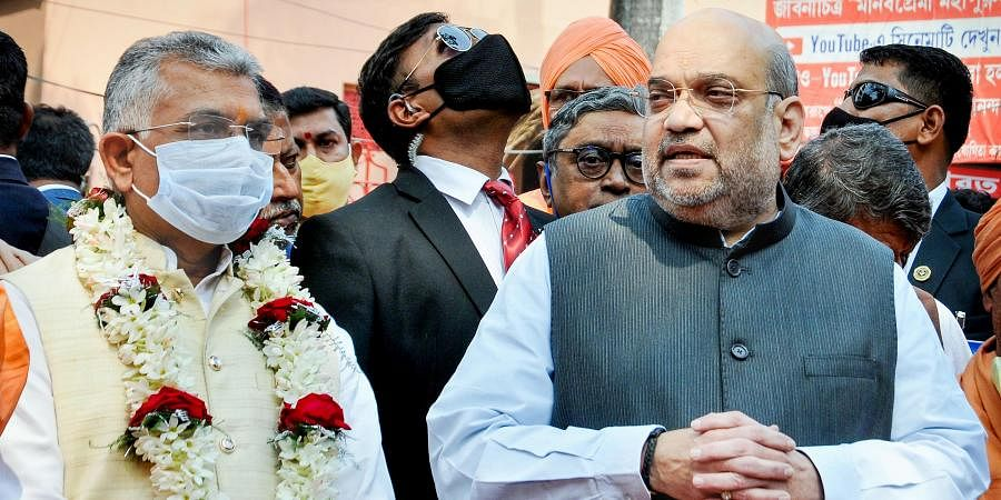 Union Home Minister Amit Shah interacts with media as West Bengal BJP State President Dilip Ghosh L looks on after offering prayers at Bharat Sevashram Sangha
