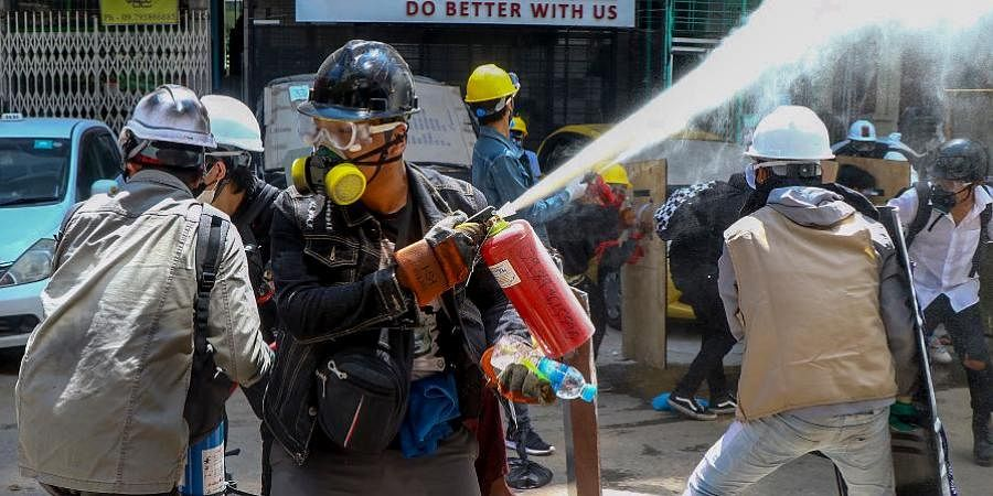 Anti-coup protesters discharge fire extinguishers to counter the impact of the tear gas fired by police during a demonstration in Yangon, Myanmar.