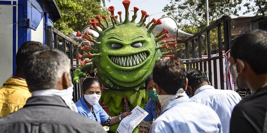 A BMC volunteer wearing coronavirus themed costume participates in a COVID-19 awareness campaign in Mumbai. (Photo | PTI)