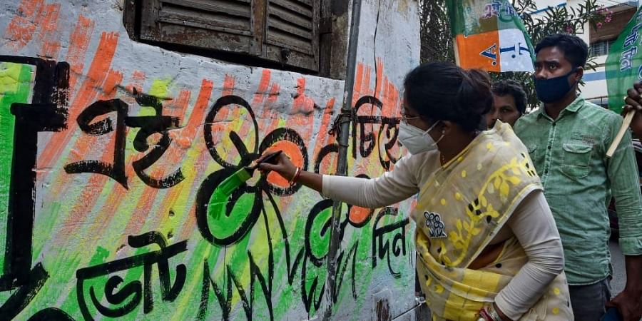Trinamool Congress candidate Shashi Panja paints party symbol on a wall during her election campaign for the Assembly polls, in Kolkata