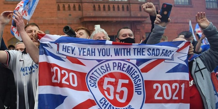 Rangers fans celebrate with flags outside Ibrox Stadium, home of Rangers Football Club, in Glasgow on March 7, 2021 after their 1st Scottish Premiership title for 10 years was confirmed.
