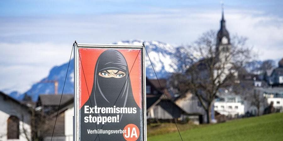 A poster supporting the initiative 'Yes to a ban on covering the face' is displayed at the village Buochs, Switzerland,