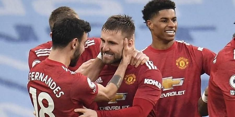 Manchester United's defender Luke Shaw (C) celebrates scoring his team's second goal againsst Manchester City at the Etihad Stadium in Manchester, north west England, on March 7, 2021.