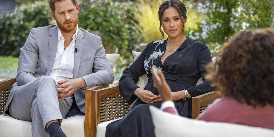 This image provided by Harpo Productions shows Prince Harry, left, and Meghan, Duchess of Sussex, in conversation with Oprah Winfrey