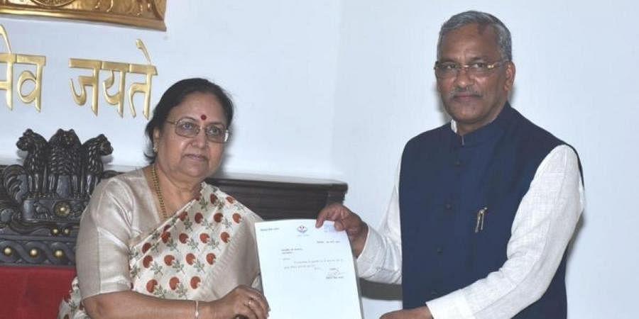 Uttarakhand governor Baby Rani Maurya (L) accepts resignation of CM Trivendra Singh Rawat