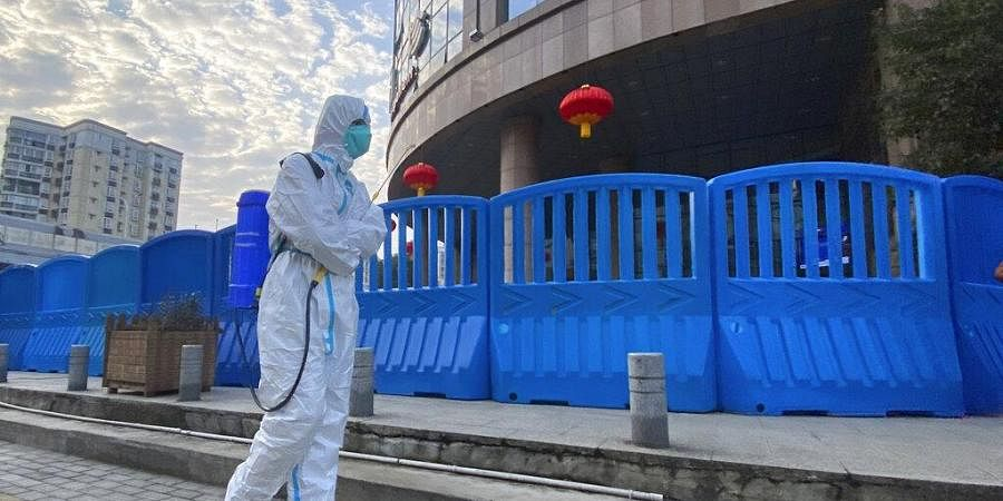 A worker in protectively overalls and disinfecting equipment walks outside the Wuhan Central Hospital