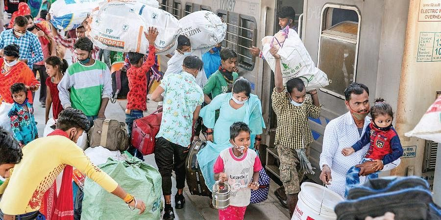 Migrants board a train at Jalandhar railway station to leave for their home states amid rise in COVID-19 cases.