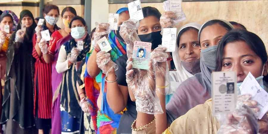 Voters show their EPIC cards before casting vote at a polling booth during the 4th phase of the West Bengal assembly election, in Howrah district