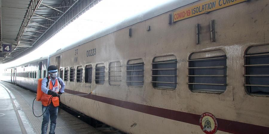 A sanitaion staffer spray disinfectant at Covid -19 Isolation Coaches at Anand Vihar railway station in Delhi as Covid-19 Isolation