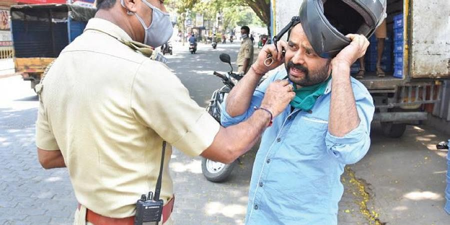 A police officer fines a motorist for not wearing a mask in Bengaluru. (Photo | Vinod Kumar T, EPS)