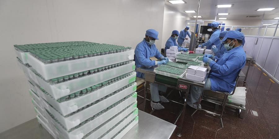 Employees pack boxes containing vials of AstraZeneca's Covishield vaccine at the Serum Institute of India in Pune.