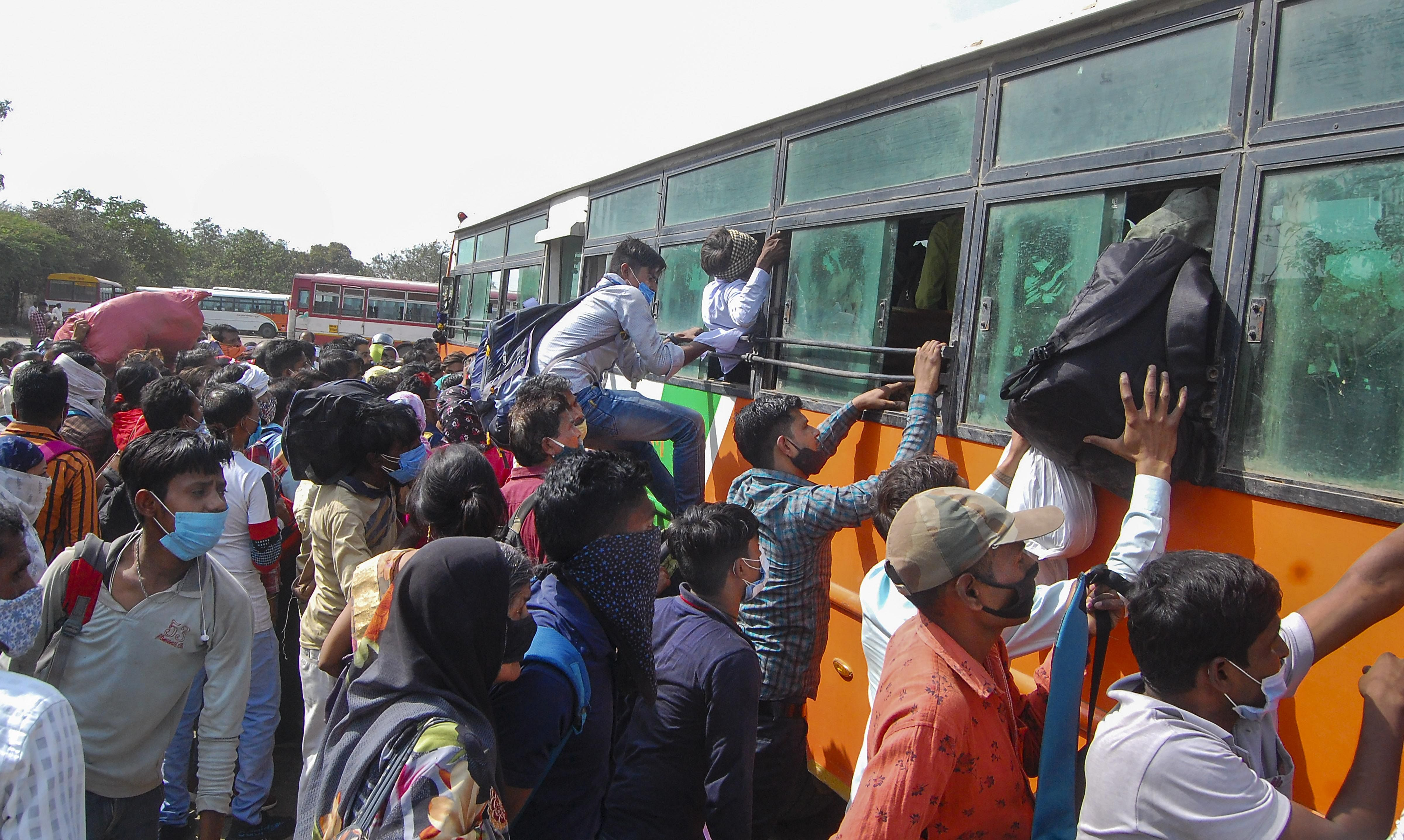 Migrants board buses for their native places amid surge in COVID-19 cases, at Jhakakati Bus Stand in Kanpur