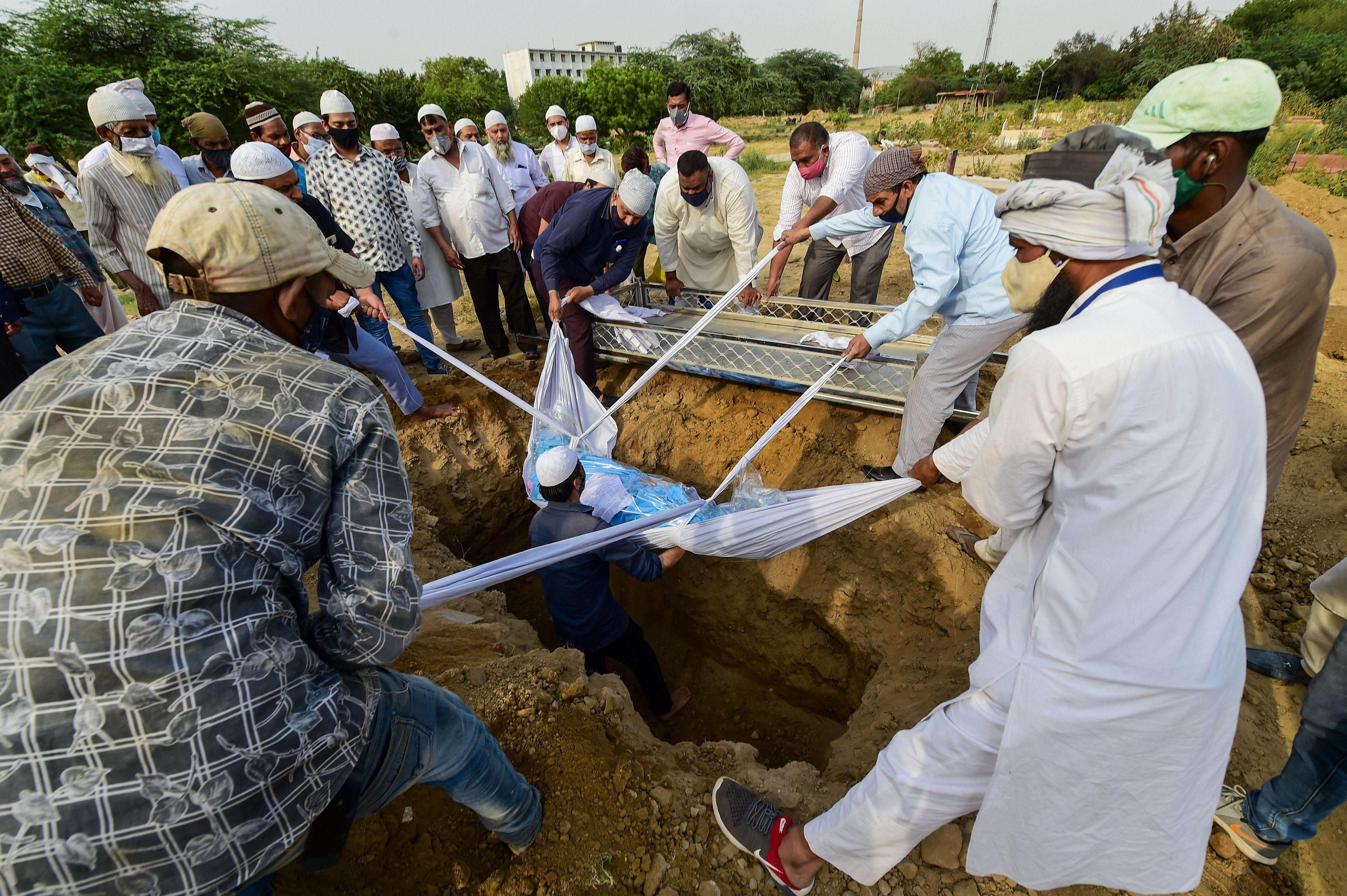 Burial of a person who died of COVID-19, amid a spike in coronavirus cases countrywide, at a graveyard in New Delhi