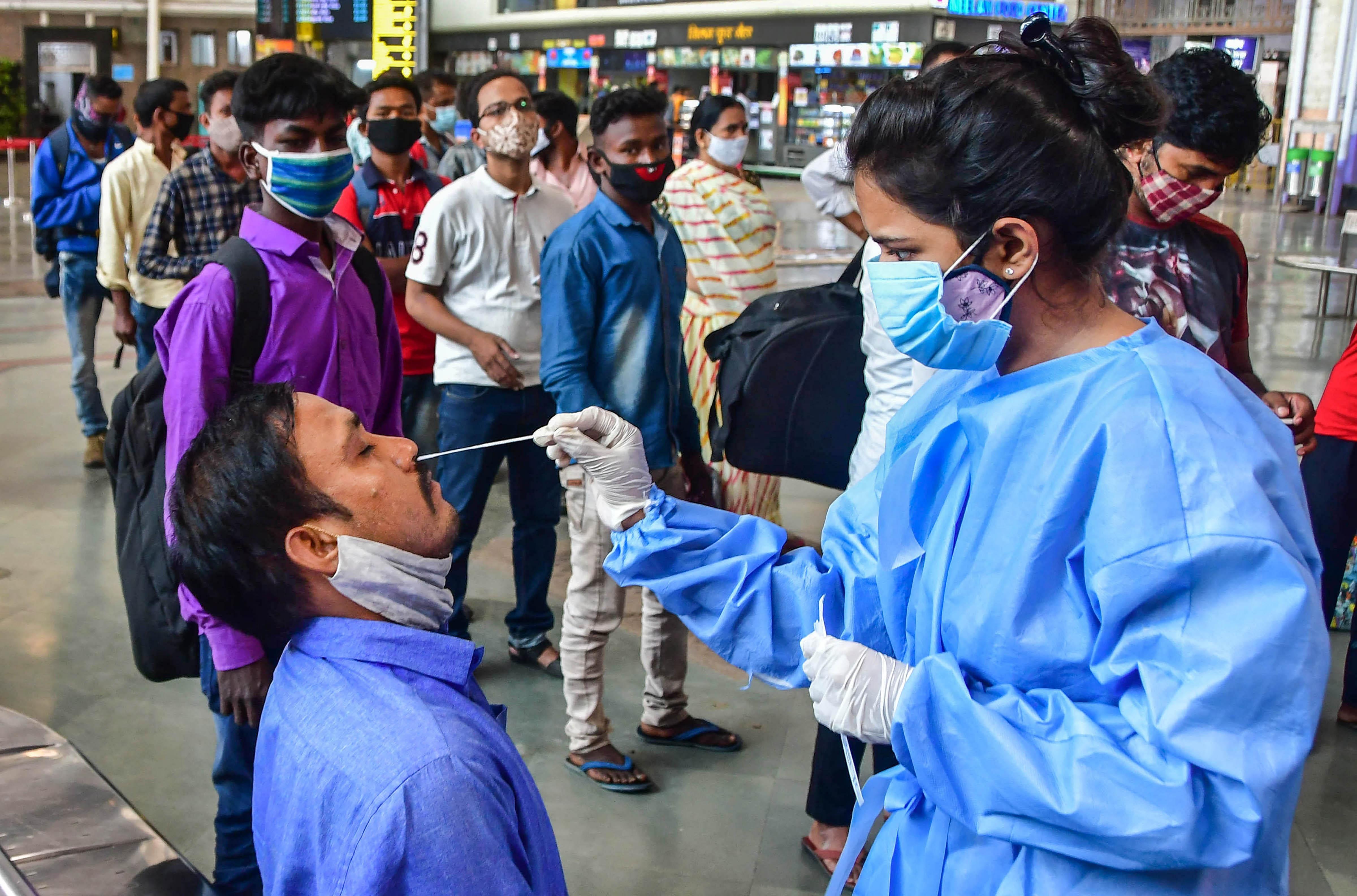 A health worker take swab samples of passengers at Chhatrapati Shivaji Maharaj Terminus Railway Station, amid spike in Covid-19 cases, in Mumbai
