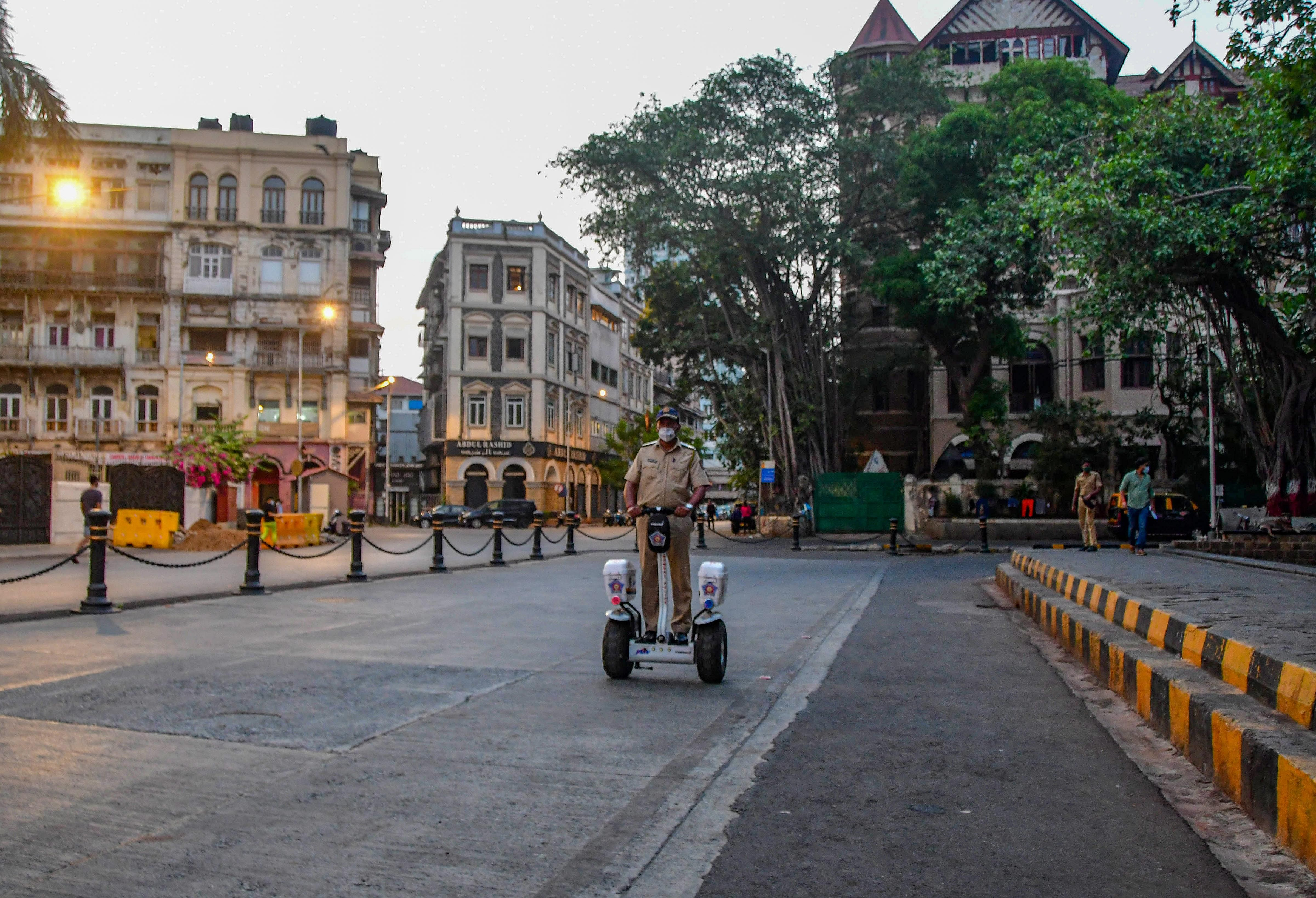 A police personnel patrols near the Gateway of India area, before the start of the 15-day curfew due to a surge in COVID-19 cases in Mumbai
