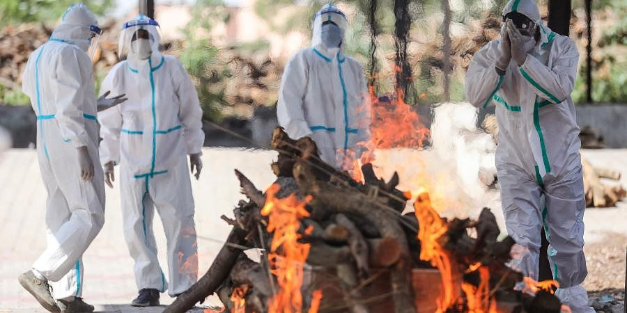 Health workers and family members, wearing protective suits, perform the last rites of a person who died of COVID-19, at Shakti Nagar Cremation Ground in Jammu
