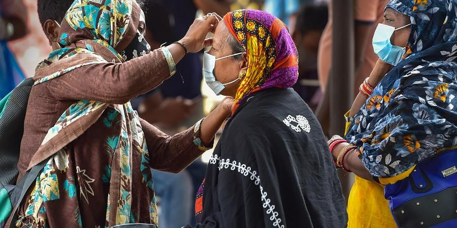 A woman helps an old lady to wear face mask at Bengaluru City Railway Station amid surge in coronavirus cases