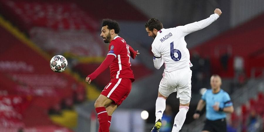 Liverpool's Mohamed Salah, left, jumps for the ball with Real Madrid's Nacho during a Champions League quarter final second leg soccer match. (Photo | AP)