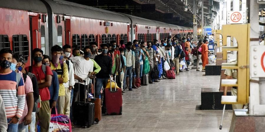 Migrants stand in a queue to give the samples for COVID-19 testing amid the rise in cases, at Patna Junction railway station