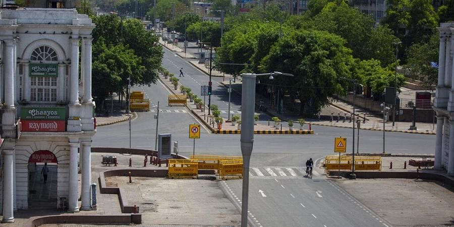 A cyclist pedals past a deserted street during a weekend lockdown in New Delhi