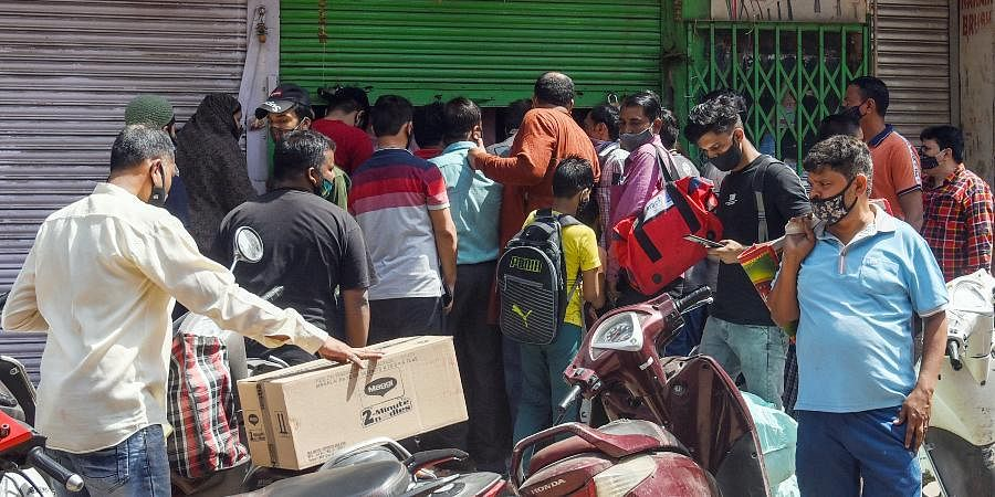 People rush to ration shops to buy essential things after the Delhi government imposes a one-week curfew