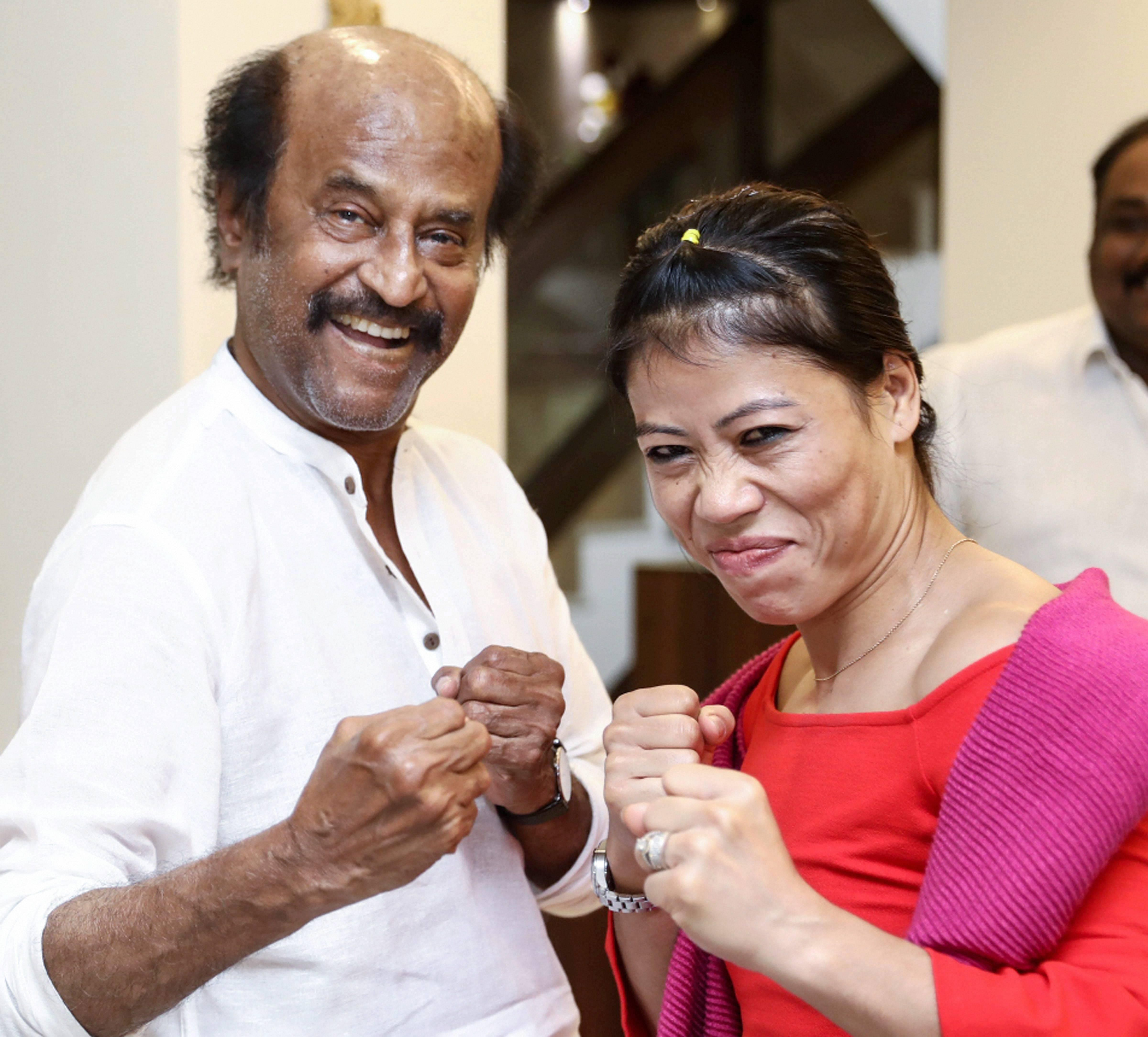 Rajinikanth (L) strikes a pose with boxing icon Mary Kom at his residence