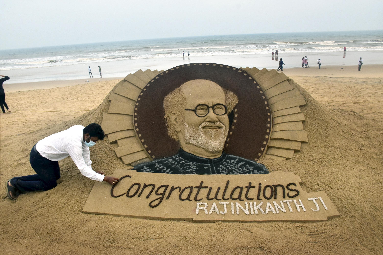 Sand artist Sudarshan Patnaik makes a sand art of actor Rajinikanth on being selected for the DadaSahebPhalke Award