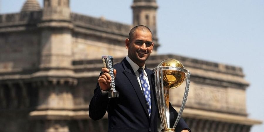 Mahendra Singh Dhoni poses with the Man of the match and the ICC Cricket World Cup trophy near the Gateway of India. (Photo | AFP)