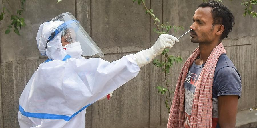 A health worker takes sample from a man for COVID-19 test, as coronavirus cases surge across the country.