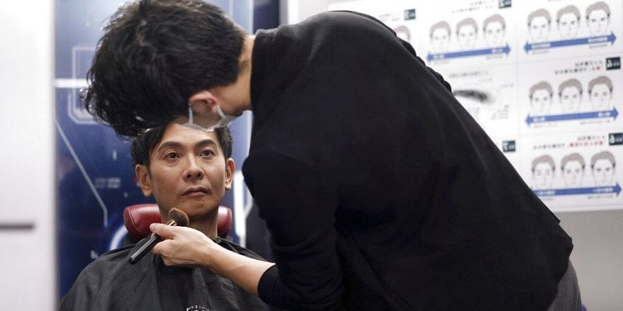 Yoshihiro Kamichi, a 44-year-old office worker, receives makeup and gets his hair done by a makeup artist at Ikemen-Works, a makeup salon for men, in Tokyo Wednesday, Feb. 3, 2021.
