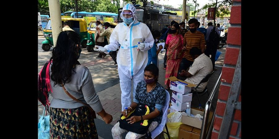 A healthcare worker prepares to collect a swab sample from a passenger at the Kempegowda Bus Station in Bengaluru on Sunday. (Photo | Shriram BN, EPS)