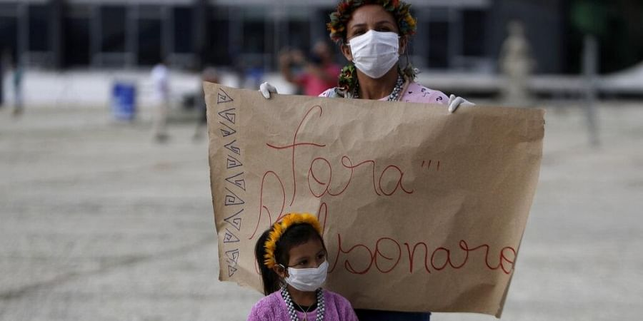 An Indigenous woman with her daughter holds the Portuguese sign 'Get out Bolsonaro' to protest Brazilian President Jair Bolsonaro's proposals to allow mining on Indigenous lands.