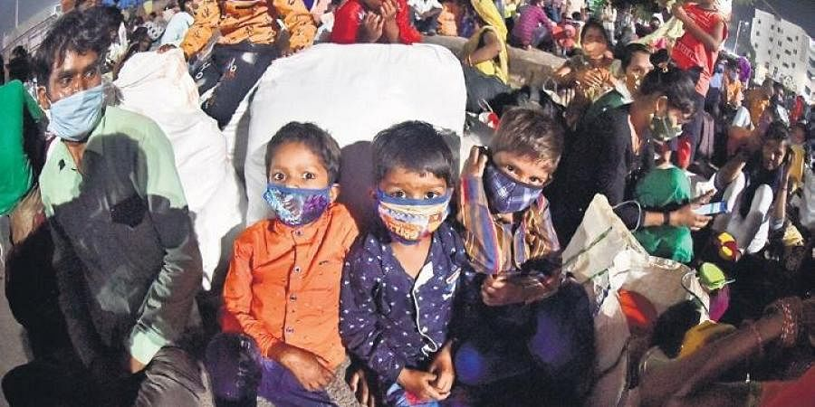 Children wearing masks were seen outside Secunderabad Railway Station on Wednesday after the State government announced night curfew   Vinay Madapu