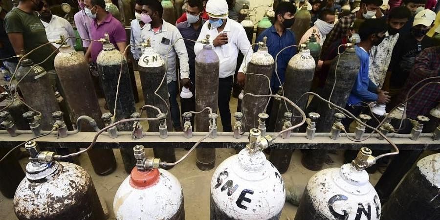 People refill medical oxygen cylinders for Covid-19 coronavirus patients at an oxigen refile station in Allahabad on April 20, 2021.