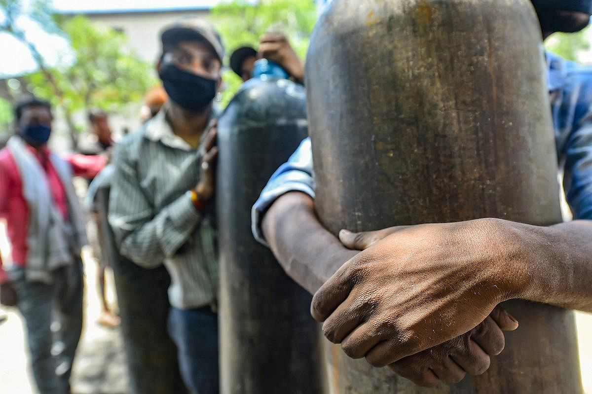 Family members of COVID-19 patients desparately wait to fill their empty cylinders with medical oxygen in Kanpur. (Photo | PTI)