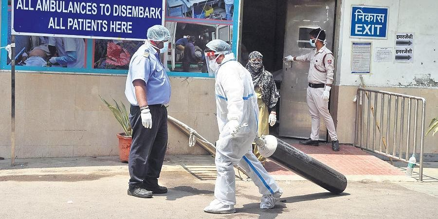 A health worker moves oxygen cylinders at a hospital in New Delhi on Friday.