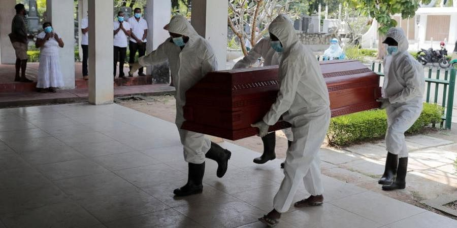 Sri Lankan health workers carry a coffin carrying remains of a COVID -19 victim to a cremation furnace as relatives watch from a distance in Colombo.