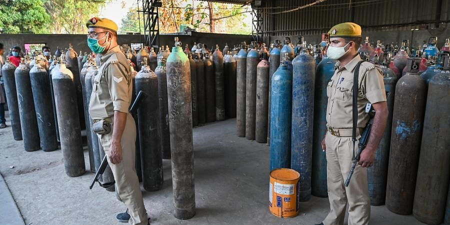 Policemen keep vigil as family members of COVID-19 patients wait to fill their empty cylinders with medical oxygen in Prayagraj