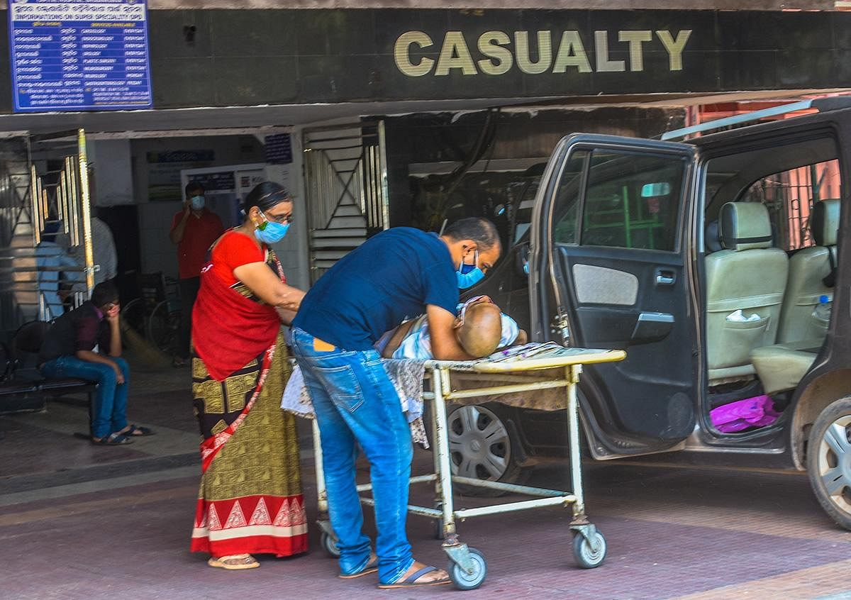 Relatives shifting an elderly person on to a stretcher outside the casualty ward of a hospital in Bhubaneswar. (Photo | Biswanath Swain, EPS)
